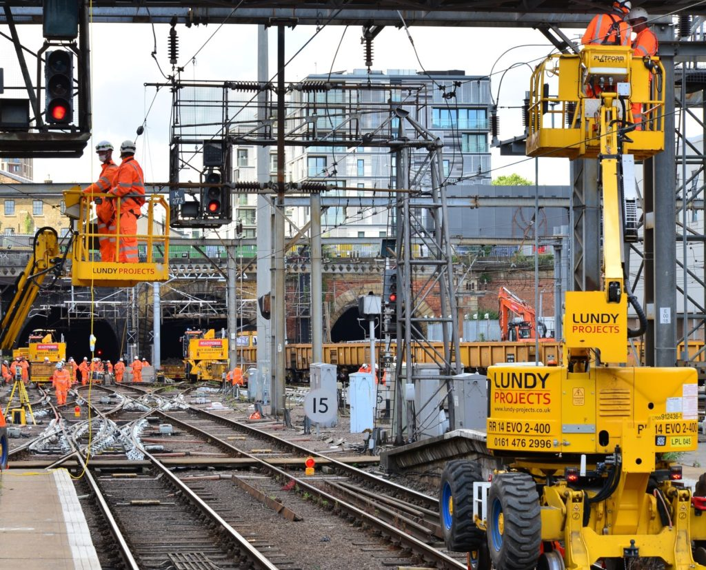Engineers work on the tracks and overhead line equipment at London King's Cross station.